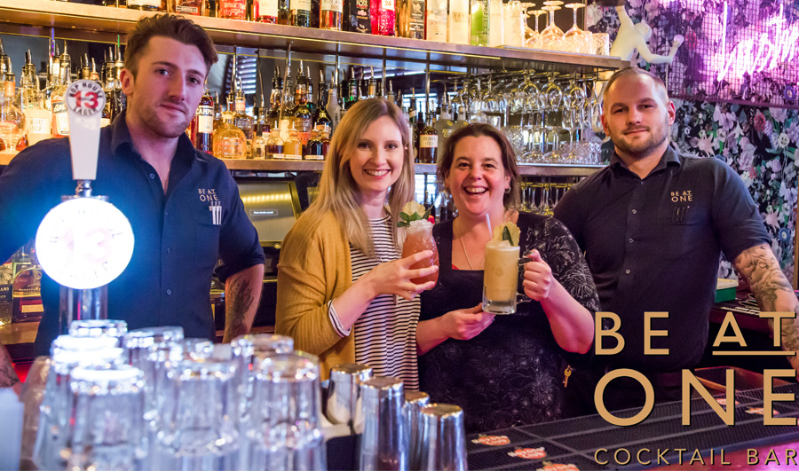 Four people standing behind a bar holding cocktails