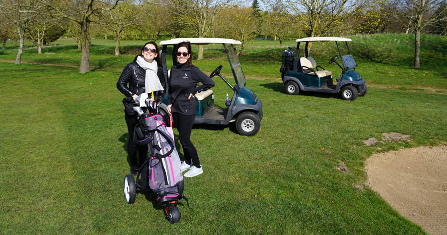 Two ladies standing in front of a set of golf clubs