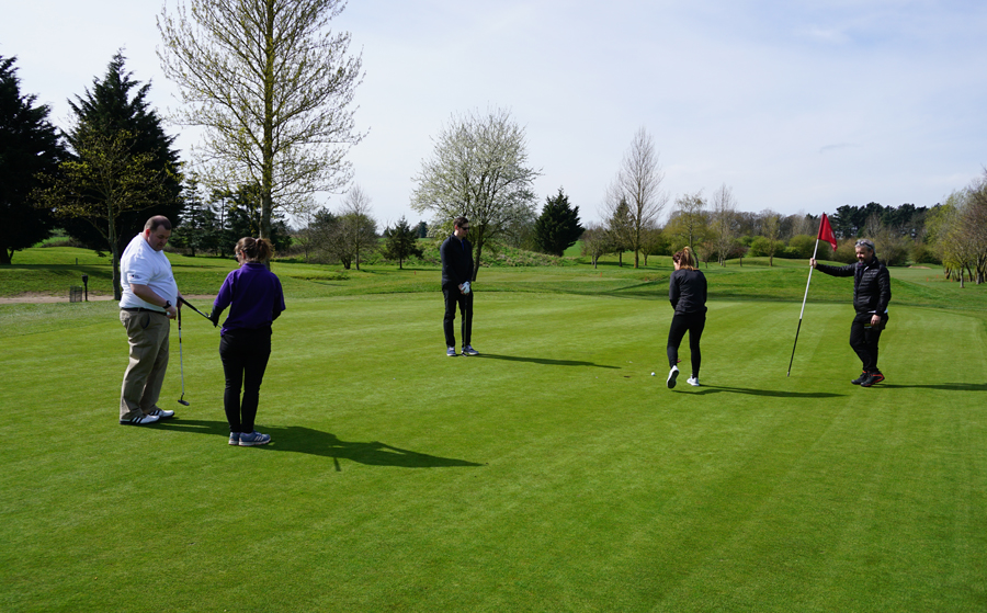 group of people standing on putting green