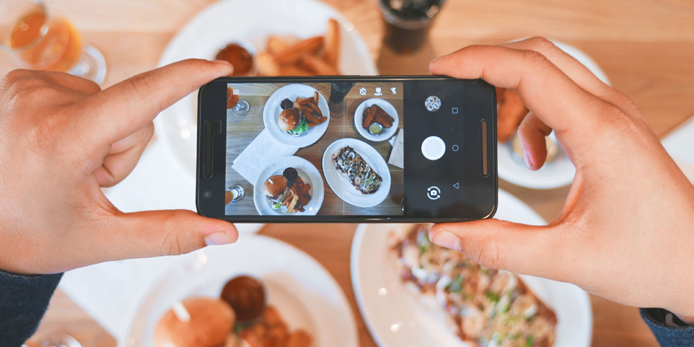 Person taking a photo of food on phone