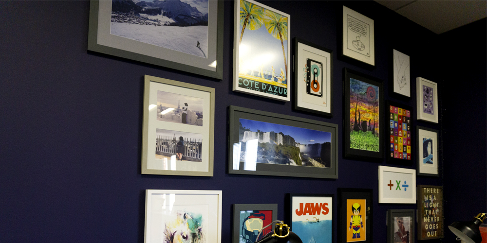 Picture frames with images hanging on purple wall