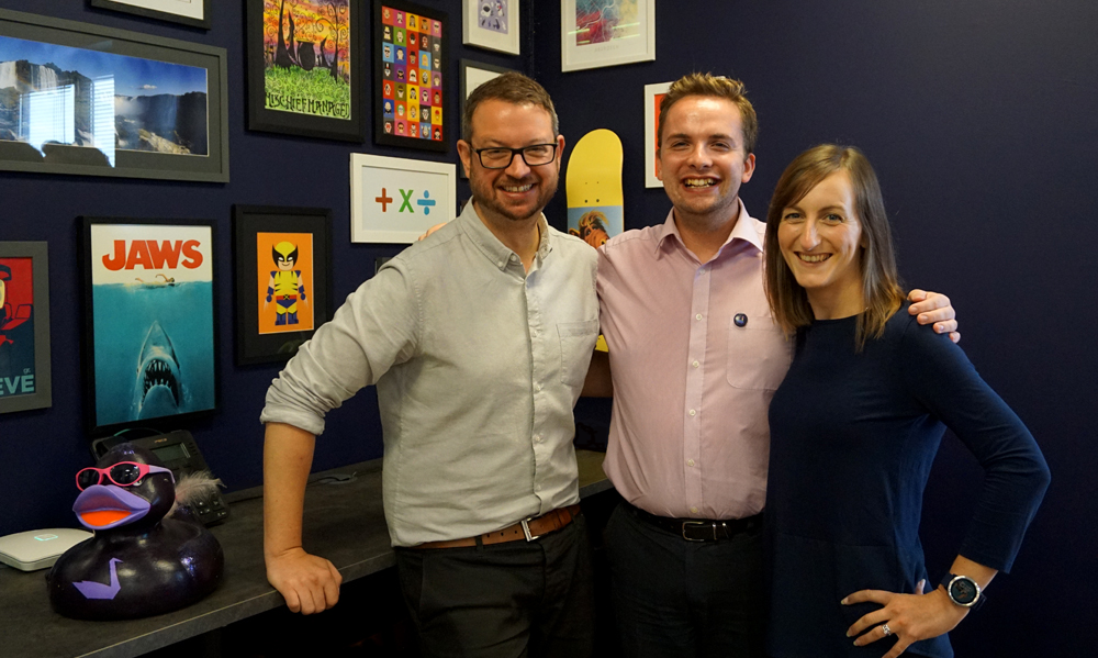 Aimee, Alex and James standing in front of picture wall