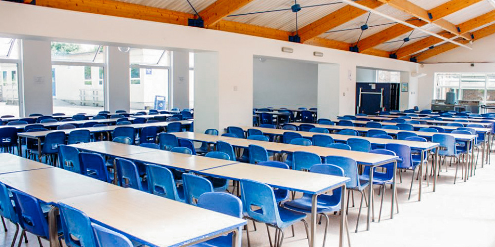 Tables and chairs lined up in a classroom
