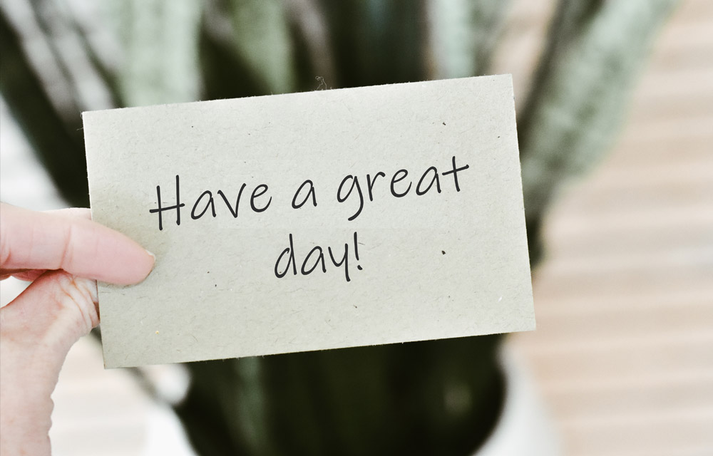 Hand holding a paper note saying have a great day