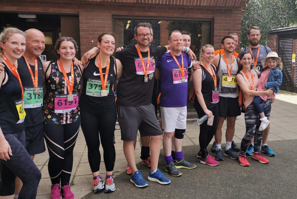 indigo Swan team members in running gear wearing medals